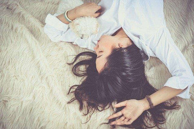 žena vzhůru nohama, leží na kožešině a má v ruce malého chlupatého bílého pejska
