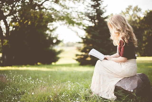 žena s dlouhými blonďatými vlasy sedí na kameni v přírodě, čte si knihu